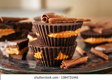 Tasty chocolate peanut butter cups on plate, closeup