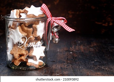 Tasty Christmas Cookies in Transparent Pot with Silver Bells, Isolated on Vintage table Background.