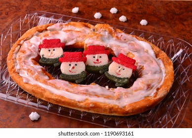 A tasty Christmas treat with snowman candles around the delicious Kringle.