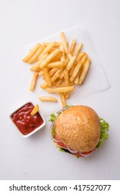 tasty classic homemade hamburger on white table with fries
