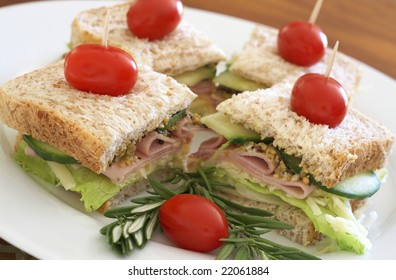 Tasty club sandwich with green lettuce, cheese, smoked ham and wholegrain mustard on wholewheat bread with rosemary and tomatoes on white plate