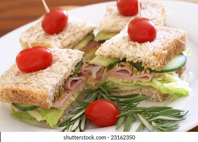 Tasty club sandwiches with green lettuce, grated cheese, smoked ham and wholegrain mustard on wholewheat bread with rosemary and tomatoes