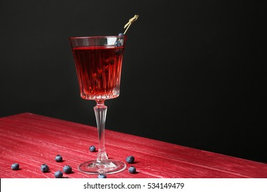 Tasty cocktail and berries on red wooden table and black background