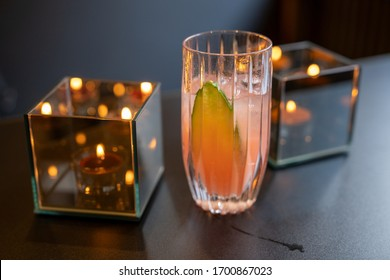 Tasty cocktail with cucumber standing between two candles