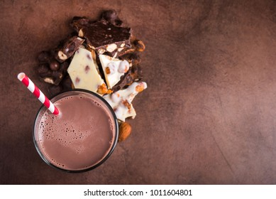 tasty cocoa drink with chocolate dessert bar on stone table, top view