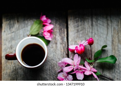 tasty coffee in a cup and a sprig of pink flowers on a wooden table