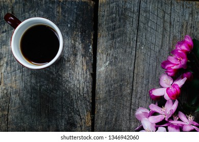 tasty coffee in a traditional Turkish cup and a sprig of pink flowers on a wooden table