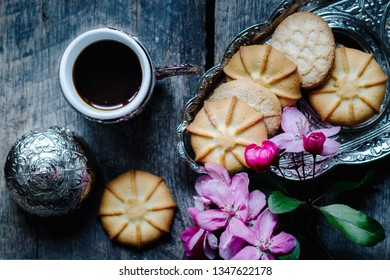 tasty coffee in a traditional Turkish cup and butter cookies and a sprig of pink flowers on a wooden table - flat lay food background