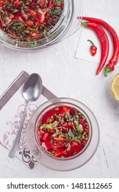 Tasty cold vegetarian raw eating soup (borscht) with beetroot, vegetables and greens in bowl on white table. Traditional russian ukrainian soup (borscht)