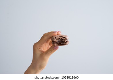 Tasty colorful bite chocolate macaroons in female hand isolated on white