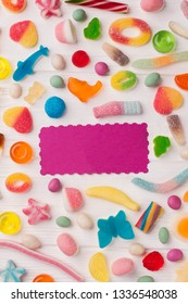 Tasty colorful candies on wooden background. Background of multicolored candies with blank paper card.