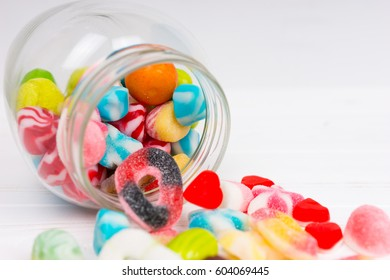 Tasty colorful chewing sweets and jelly candies fall out of the lying can on wooden white board