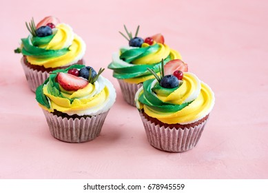 Tasty colorful cupcakes decorated with fresh berries Group of cupcakes on background Place for text