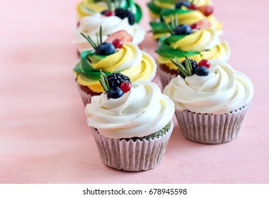 Tasty colorful cupcakes decorated with fresh berries Group of cupcakes on background