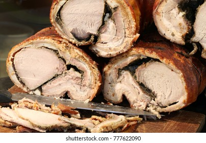 a lot of tasty cooked pork meat called PORCHETTA in Italian language for sale in the street food stall