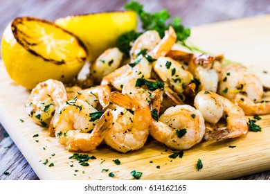 Tasty cooked shrimp seafood dinner on wood board with grilled lemon wedges