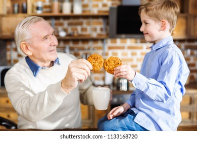 Tasty cookie. Pleasant little boy eating home made pastry with his grandfather while resting at home