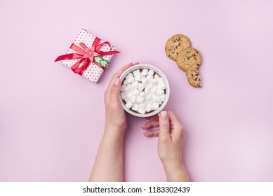 Tasty Cookies Chocolate Bars Cup of Hot Chocolate with Marshmallow Top View Flat Lay Christmas Holiday Background Christmas Beverage Pink Pastel Background Female Hand holding Cup Gift Box