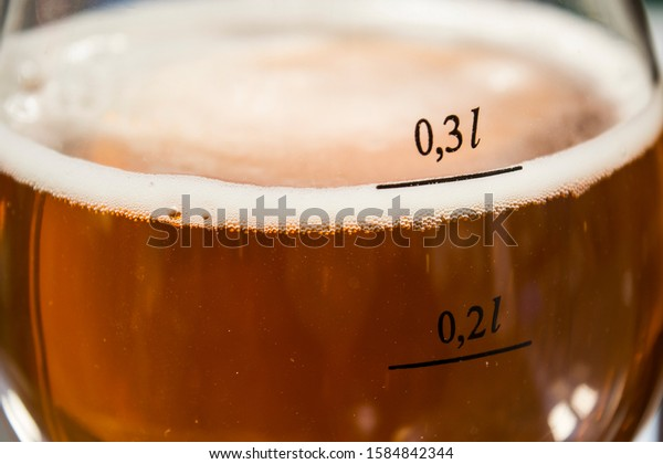 Tasty copper-colored craft beer with white bubbles in a glass with quantity markings, macro, closeup