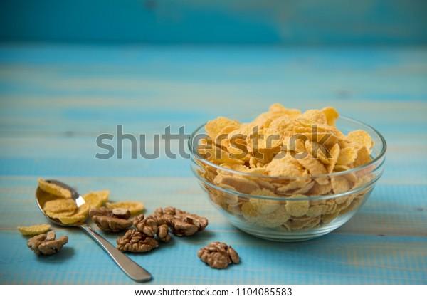 Tasty cornflakes witt walnut in glass bowl on blue background. Corn Flakes