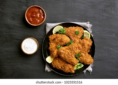 Tasty crispy chicken wings with sauce. Dish for dinner on black plate over dark stone background. Top view, flat lay