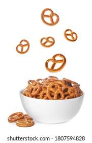 Tasty crispy pretzel crackers falling into bowl on white background