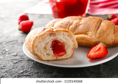 Tasty croissants with strawberry jam on plate, closeup