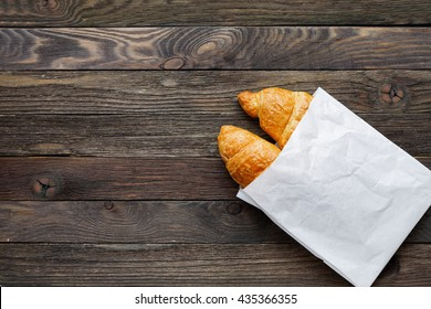 Tasty croissants in white paper bag. Rustic wooden background with sweet dessert. Top view.