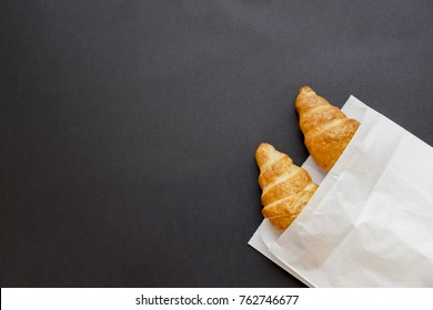 Tasty croissants in white paper bag. black background with sweet dessert. Top view. flat lay. copy space for text