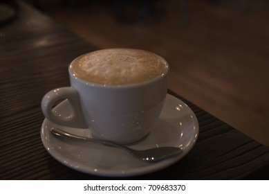 A tasty cup of cappuccino on the wooden table