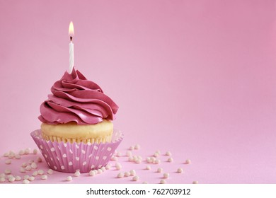 Tasty cupcake with candle on color background