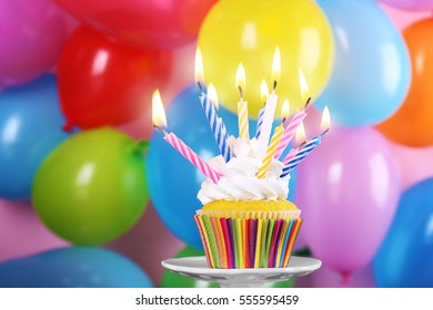 Tasty cupcake with candles on colorful background
