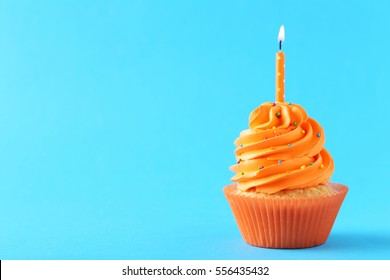 Tasty cupcake with candles on a mint background