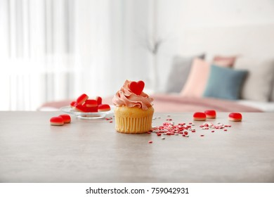 Tasty cupcake with jelly candy on table