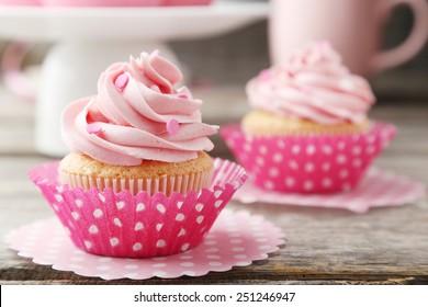 Tasty cupcake on grey wooden background