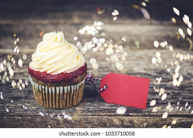 Tasty cupcake with red label for your text on the wooden boards.