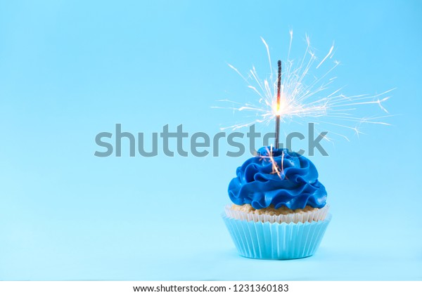 Tasty cupcake with sparkler on color background