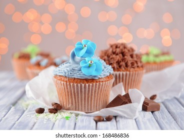 Tasty cupcakes with butter cream, on color wooden table, on lights background