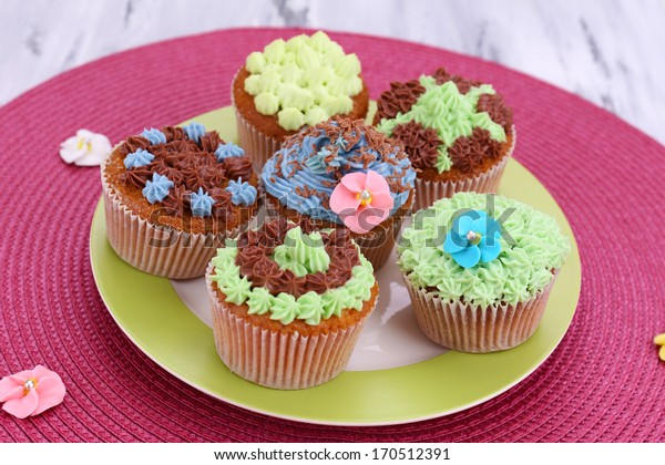 Tasty cupcakes with butter cream, on plate, on color napkin, on color wooden background
