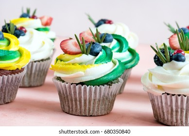 Tasty cupcakes decorated with colorful cream cheese and berries