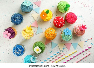 Tasty cupcakes and party decor on light background