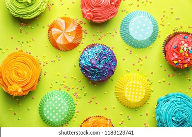 Tasty cupcakes with sprinkles and baking cups on color background