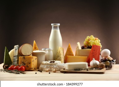 Tasty dairy products on wooden table, on dark background
