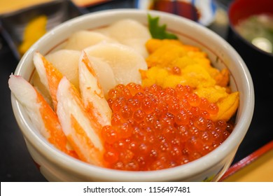 Tasty and delicious Donburi or Japanese rice bowl topped with boiled Kani(crab) Ikura(Salmon Roe) and creamy Uni(Sea Urchin) at restaurant. Closeup. Selective Focus. Healthy Eating, Eat Well Concept.