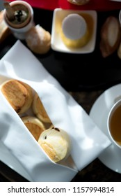 Tasty and delicious freshly baked scones with variety of sweets and desserts and a cup of tea for afternoon tea or high tea party in elegant white setting. British way to relaxation. Natural light.