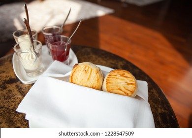 A tasty and delicious set of freshly baked scones with clotted cream and jam for afternoon tea or high tea party in elegant white setting. British way to relaxation and good time. Natural light.