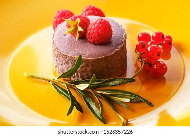 Tasty dessert cheesecake with raspberries and currants on a yellow background.
