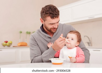 Tasty dinner. Loving young dad holding spoon and feeding baby while sitting at the table.