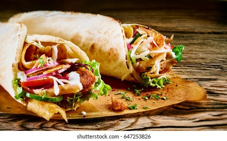 Tasty doner kebabs with fresh salad trimmings and shaved roasted meat served in tortilla wraps on brown paper as a takeaway snack