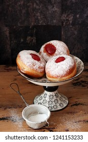 Tasty donuts with jam on wooden background